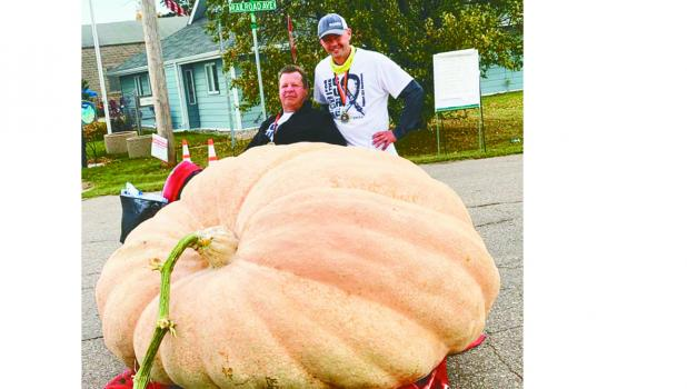 Wade Klema and JJ Solberg both of Gonvick with the record setting pumpkin in Gonvick at 1,990 pounds. Wade, who has ALS, had help from JJ Solberg on this project this last summer. Wade had developed a system of black hoses in his yard and when the sun warmed up the water in the hose he would open the hose and have a very fine mist sprayed over his pumpkin. The day was extra special with the victory as it was his birthday.