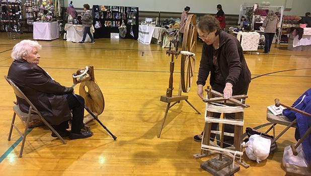 Rilla Nelson of Clearbrook showing how her grandmothers walking wheel worked at the Fiber Festival.